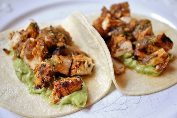 2 grilled chicken tacos with guacamole on corn tortillas on a white plate