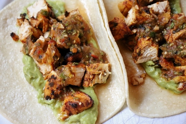 overhead view of 2 grilled chicken tacos with guacamole on corn tortillas