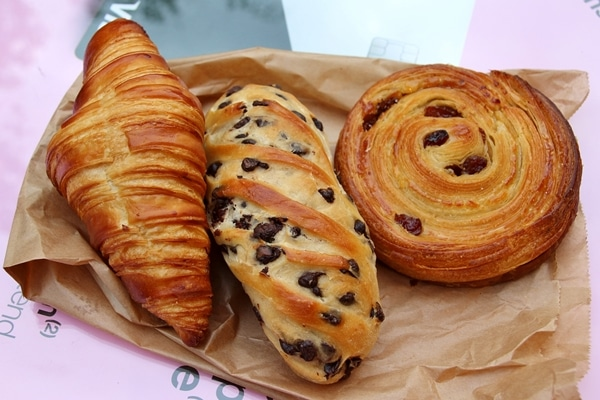 A croissant, a loaf of chocolate chip Vienna bread, and a pain aux raisins from a Parisian bakery