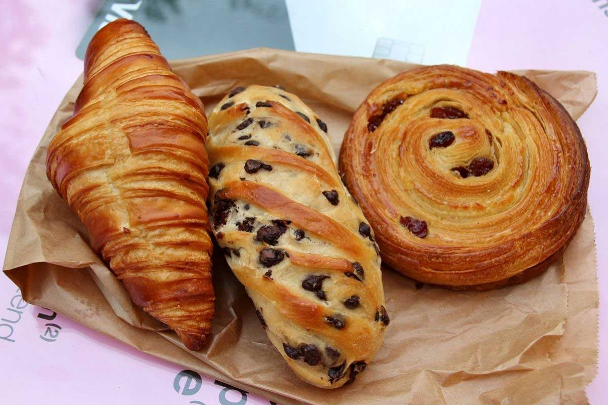 A croissant, a loaf of chocolate chip Vienna bread, and pain aux raisins.
