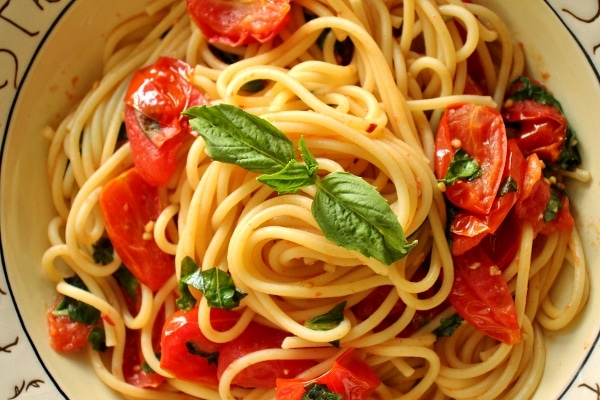 overhead view of spaghetti with a cherry tomato and basil sauce
