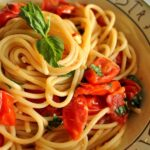 a bowl of spaghetti with tomato and basil sauce
