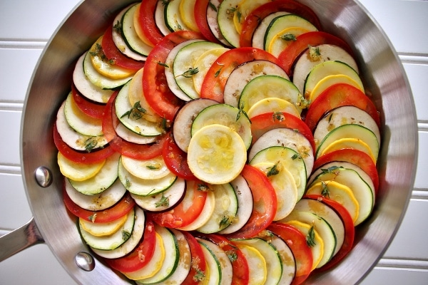 raw vegetables arranged in a spiral pattern in a skillet