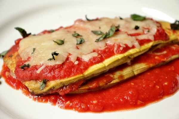 Eggplant parmesan stack on a white plate with melted cheese and fresh basil on top