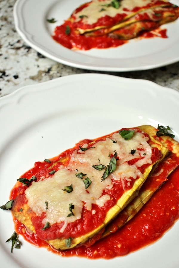 2 plates of eggplant parmesan topped with cheese and basil