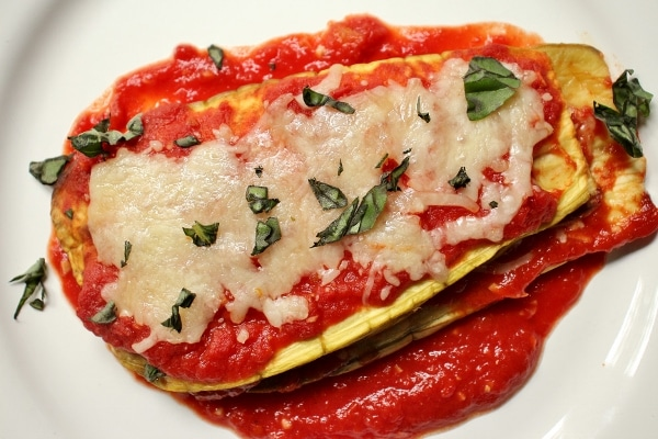 overhead view of eggplant parmesan stack on a white plate with melted cheese