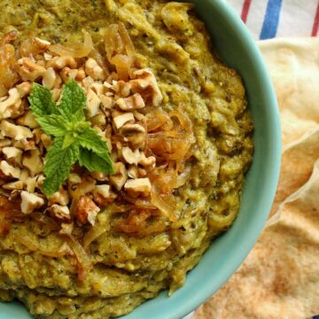 A bowl of kashke bademjan topped with walnuts and mint with pita bread on the side.