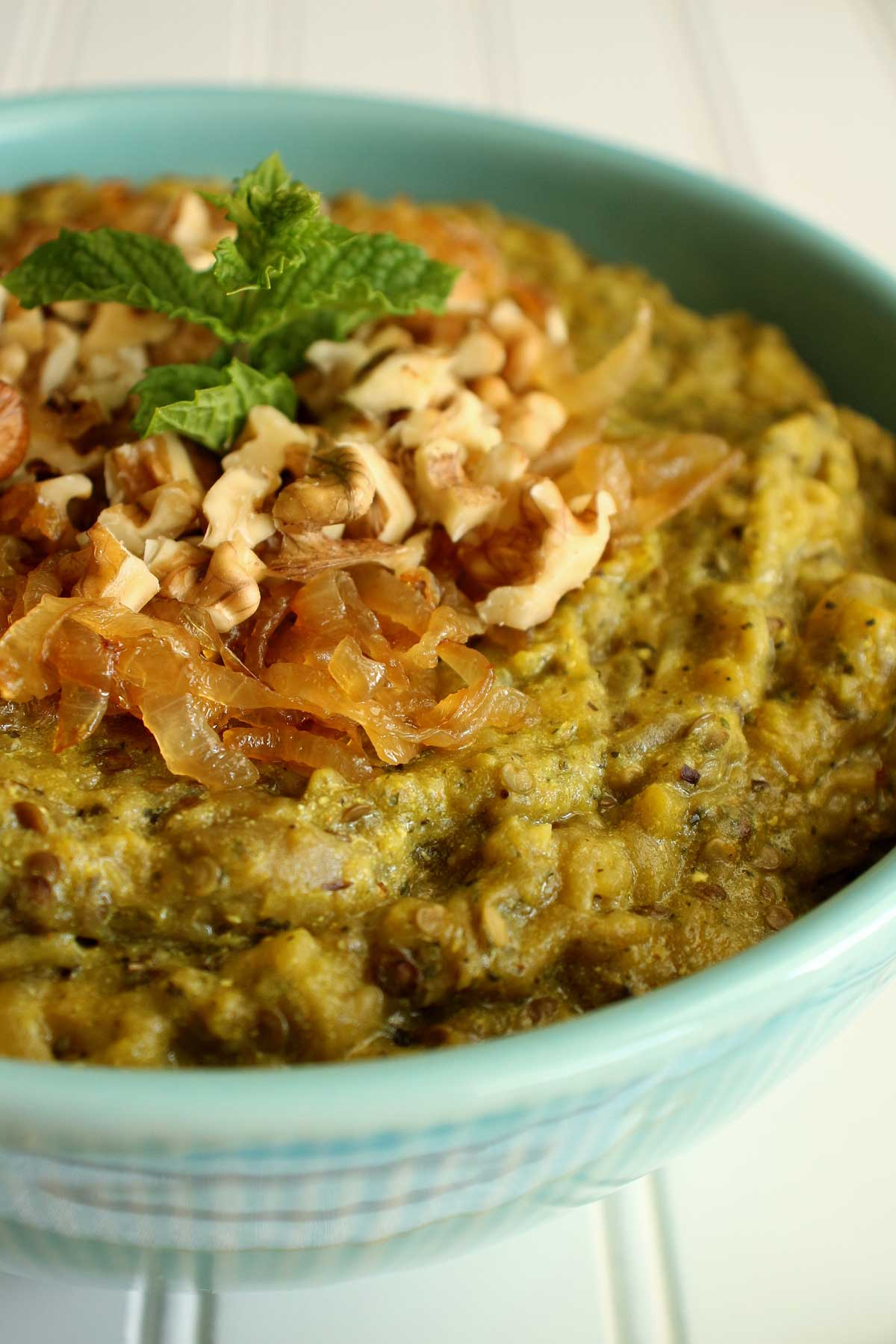 Closeup of a bowl of Persian eggplant dip garnished with caramelized onions, walnuts, and mint.