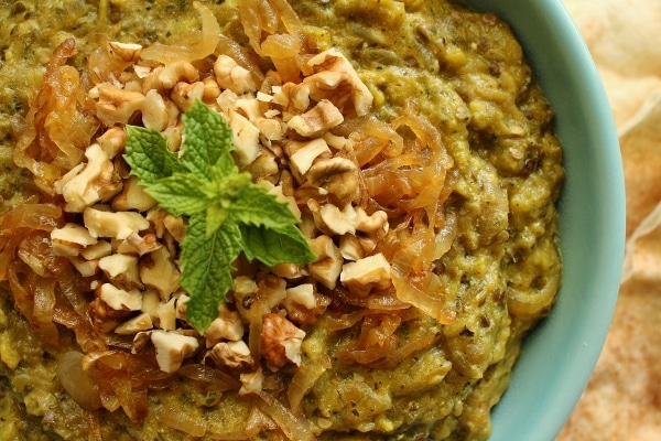 A bowl of kashke bademjan garnished with caramelized onions and walnuts