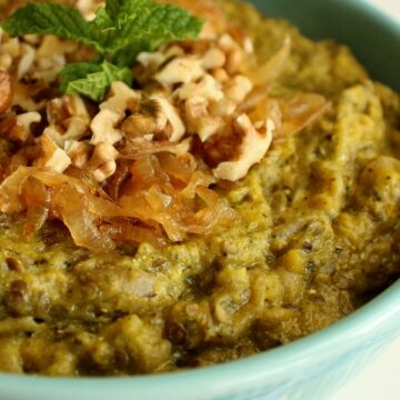 closeup of a blue bowl with eggplant dip, topped with walnuts and mint
