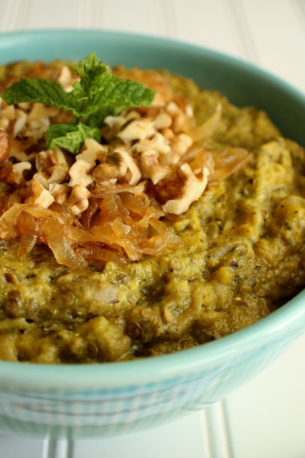 A bowl of Persian eggplant dip garnished with caramelized onions and walnuts