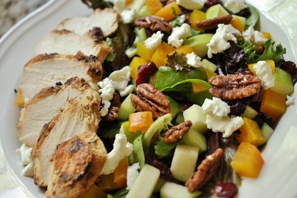 a plate of salad with grilled chicken and pecans