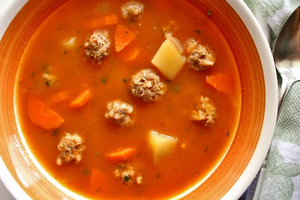 Meatball soup with potatoes and carrots in a bowl with a spoon on the side