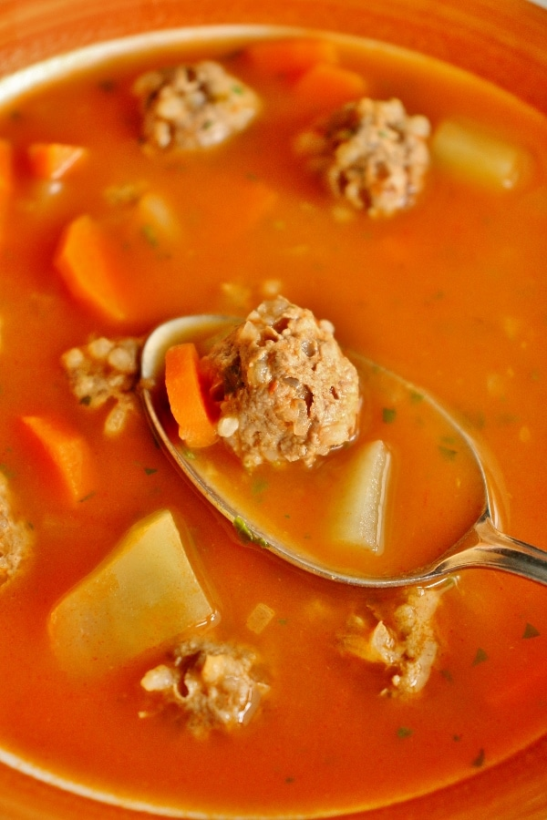 Closeup of meatball soup with potatoes and carrots in a bowl, with a spoon holding some soup over the bowl's surface