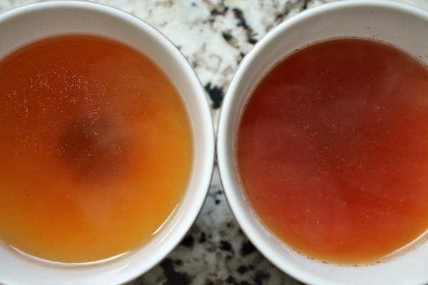 Two cups of brewed cacao tea, showing different colors based on how they were brewed