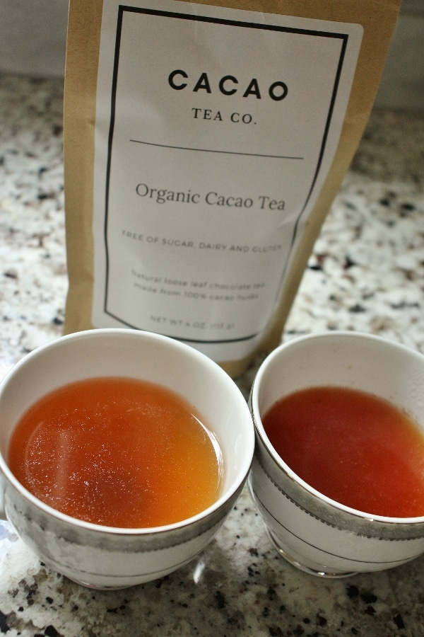 The bag of Cacao tea with two cups of brewed cacao tea in front