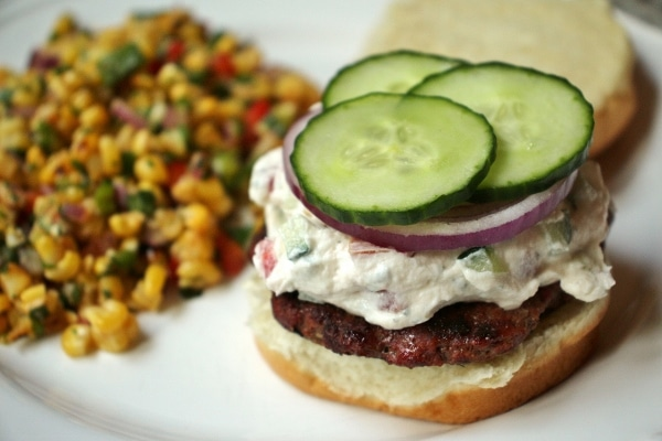 Burger with Chevre cheese, cucumbers, and red onions, with side of corn salad