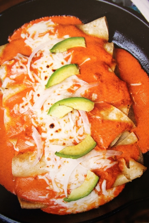 a plate of enchiladas with red sauce and cheese