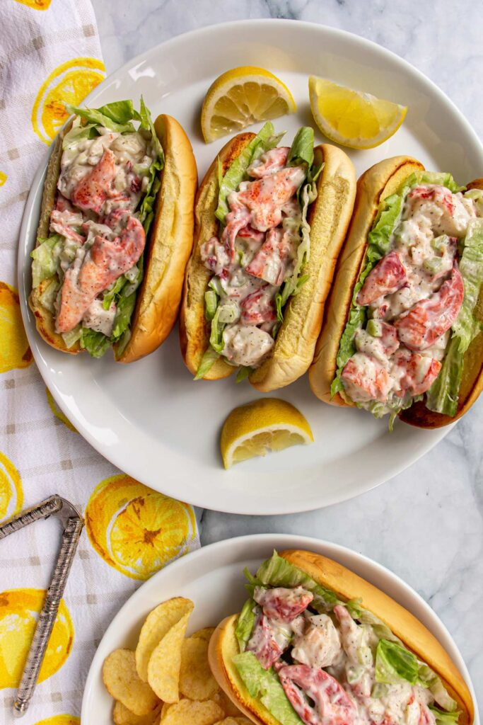 Three lobster rolls on a round platter, one lobster roll with potato chips on a plate.