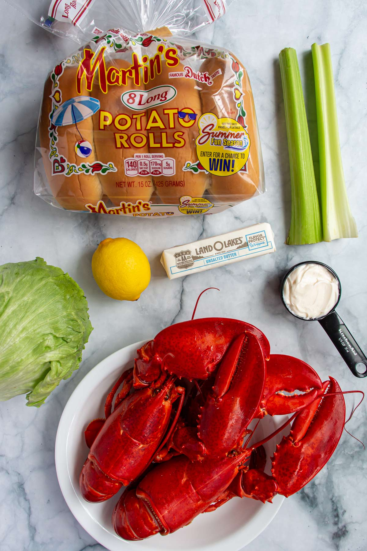 Ingredients for New England lobster rolls on a white marble background.