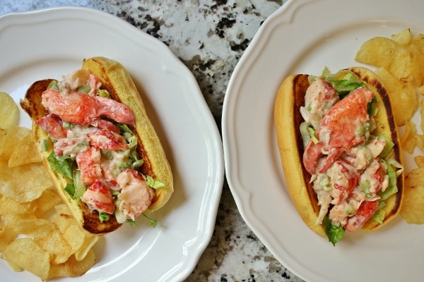 2 lobster rolls on white plates with potato chips