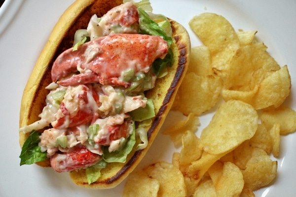 an overview picture of a lobster roll with potato chips