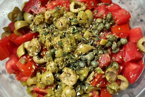 a bowl of chopped tomatoes, green olives, and capers