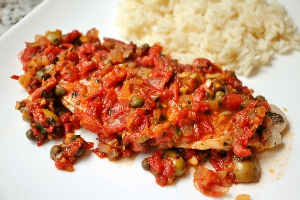 a fish fillet with a tomato and caper sauce served with white rice