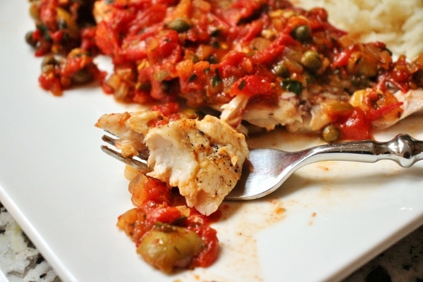 A close up of a plate of fish with a fork