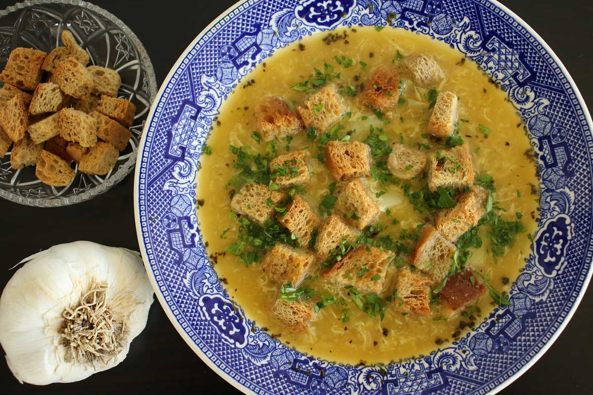 Czech garlic soup, a bowl of croutons and head of garlic next to the soup.