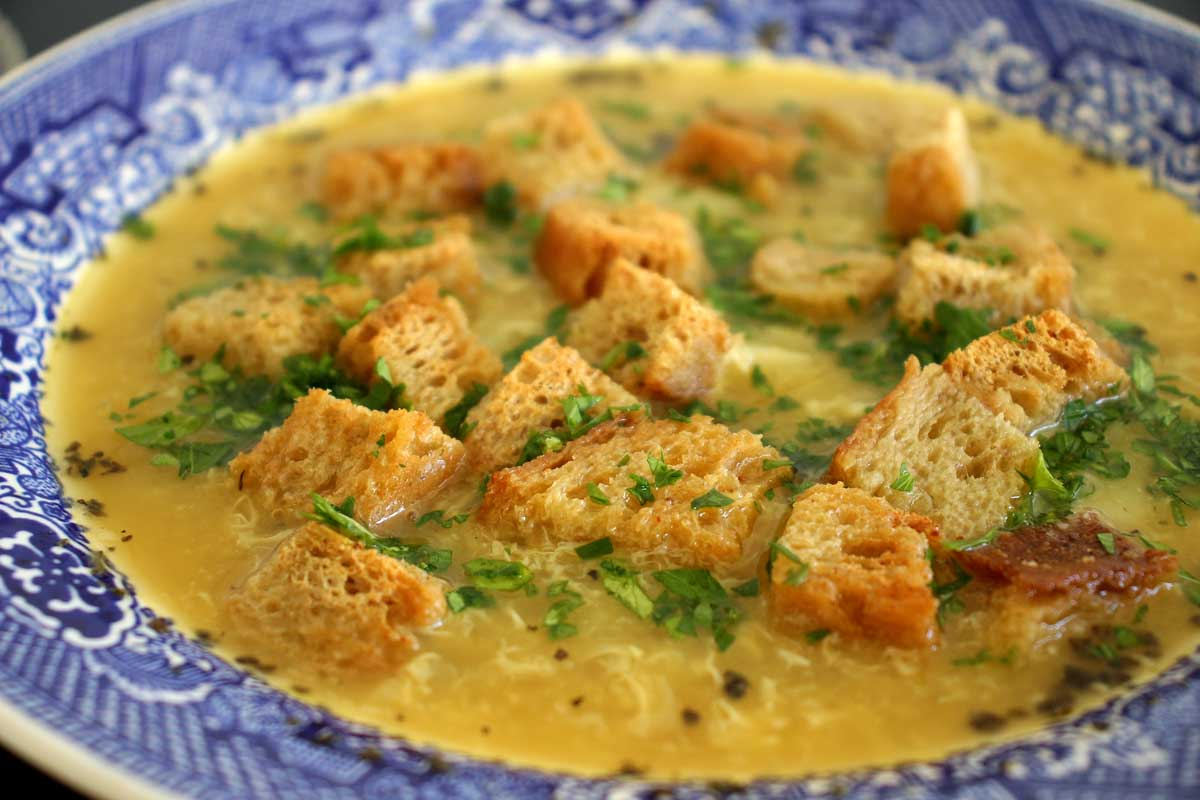 Closeup of a bowl of Czech garlic soup topped with rye croutons.