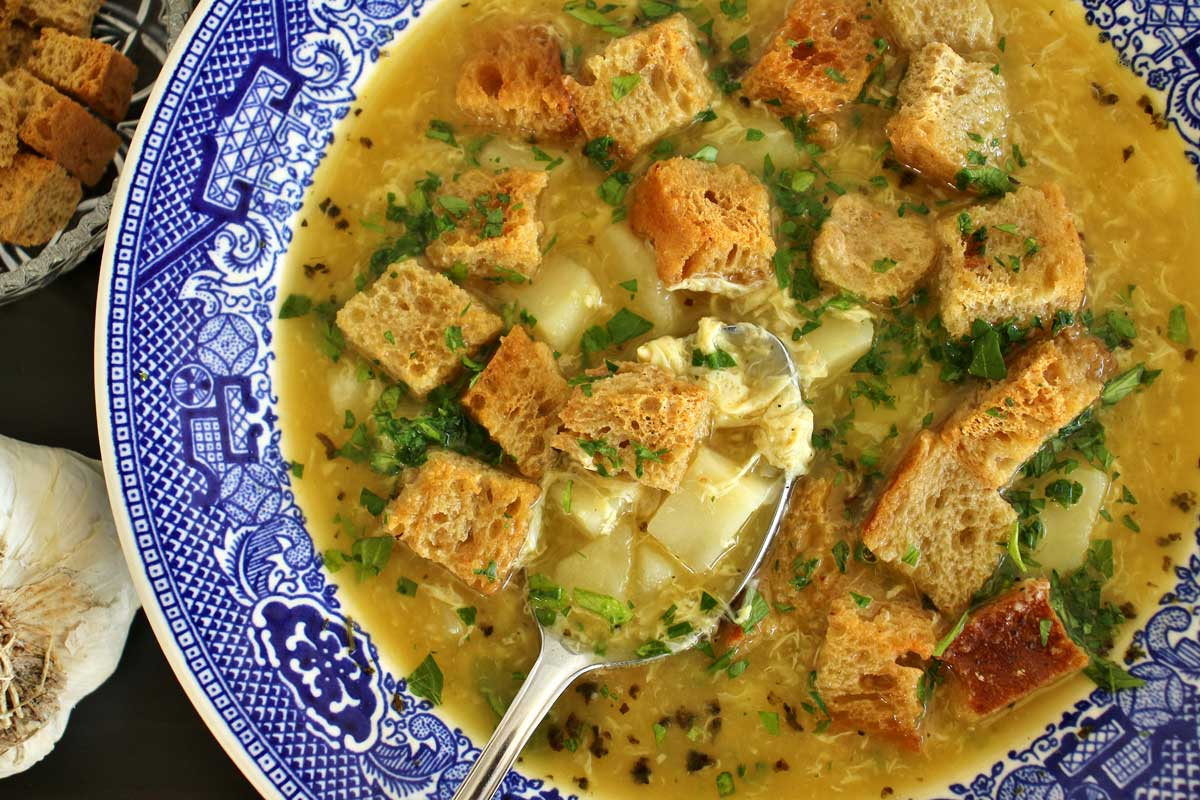 A bowl of Czech garlic soup topped with rye croutons.