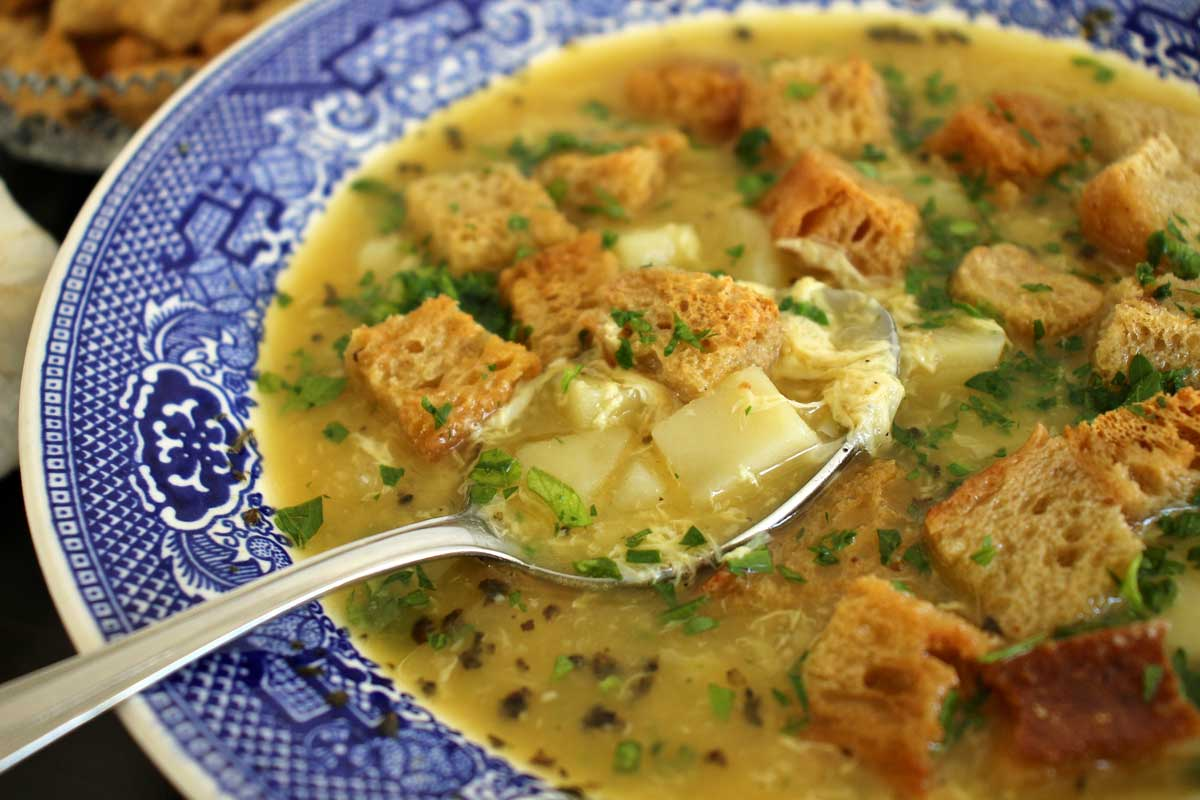 A bowl of cesnecka soup with a spoon scooping some up.