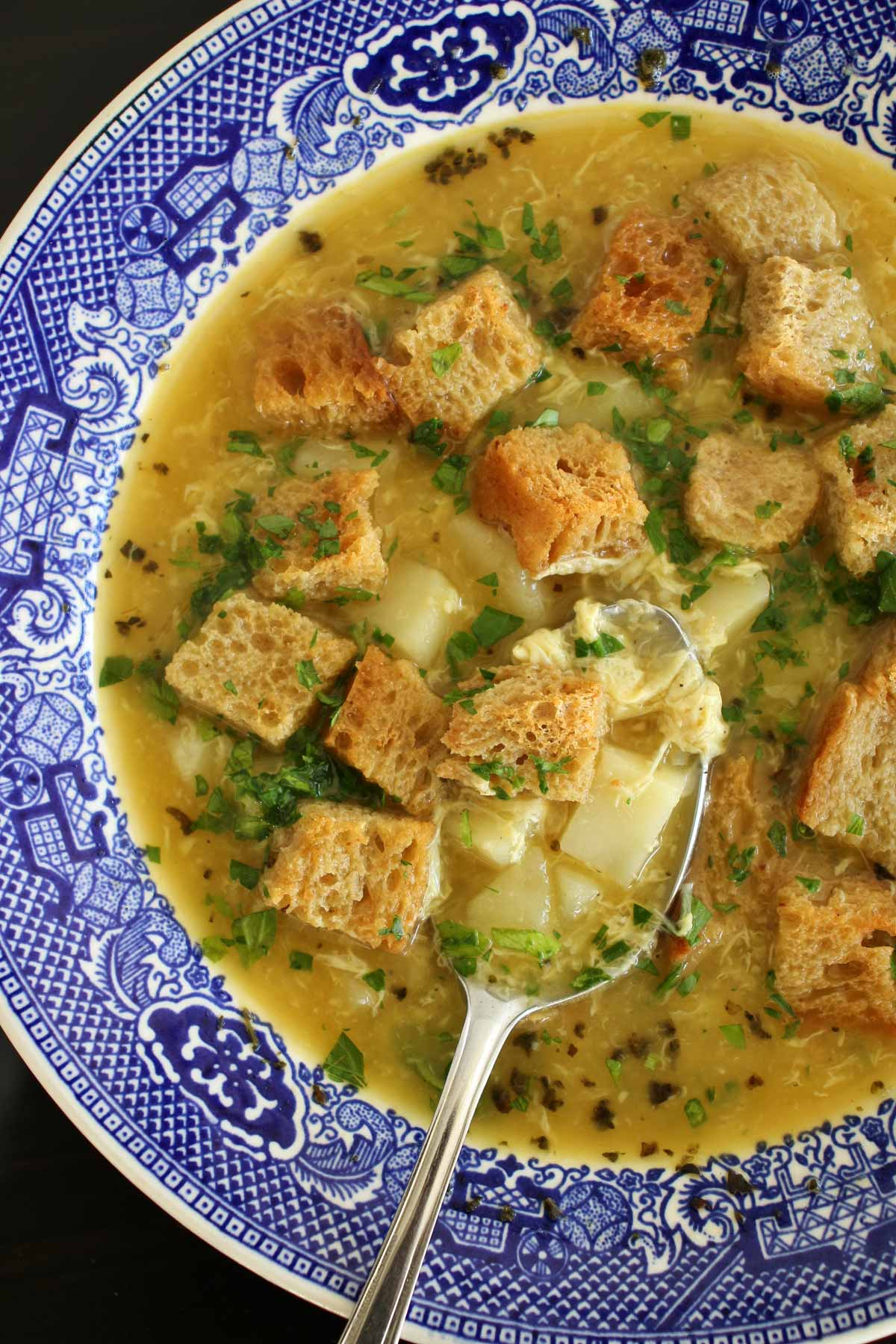 Czech garlic soup topped with rye croutons in a blue and white bowl.