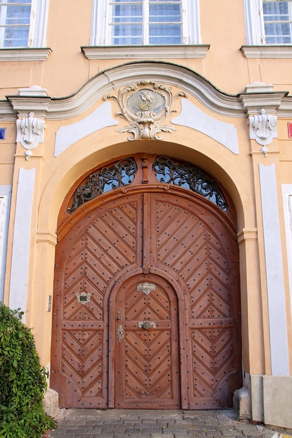closeup of a peach building with a large wooden door