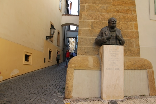 a statue of Winston Churchill at the base of a narrow cobblestone street