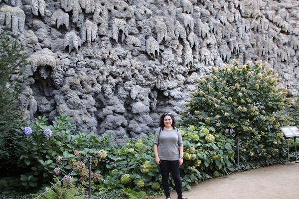 A person standing in front of a large rock