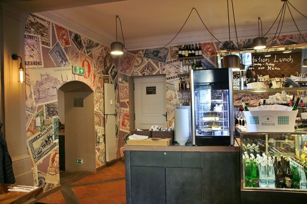 interior of a small restaurant with images of stamps on the walls