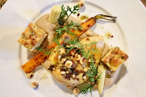 a plate of chicken with hazelnuts, carrots and bread cubes