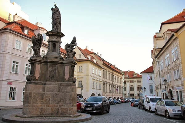 a small city square with a statue and cars