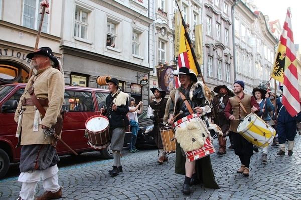 A group of people marching down the street with drums and flags