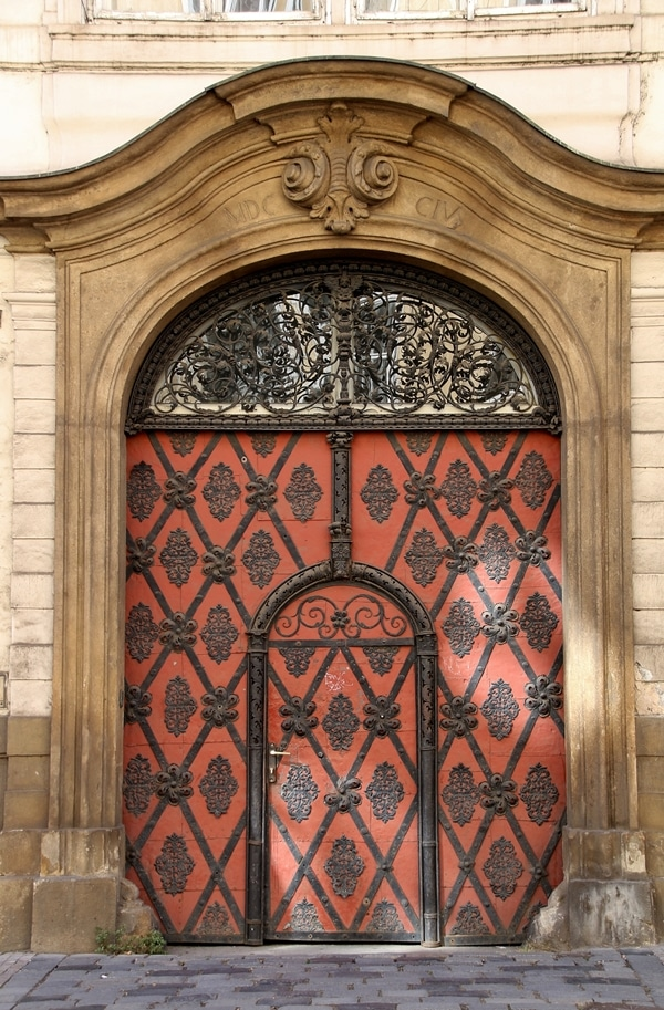 an elaborate red door with black detailing