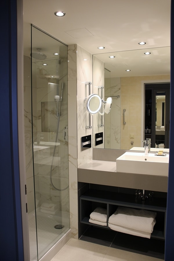 A shower, sink and large mirror in a hotel room bathroom