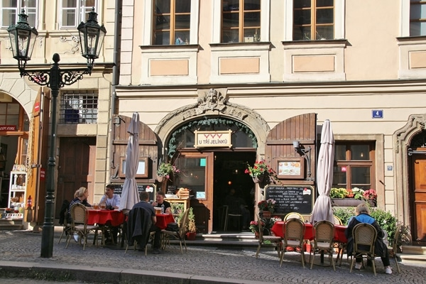 a restaurant with tables on the cobblestone sidewalk