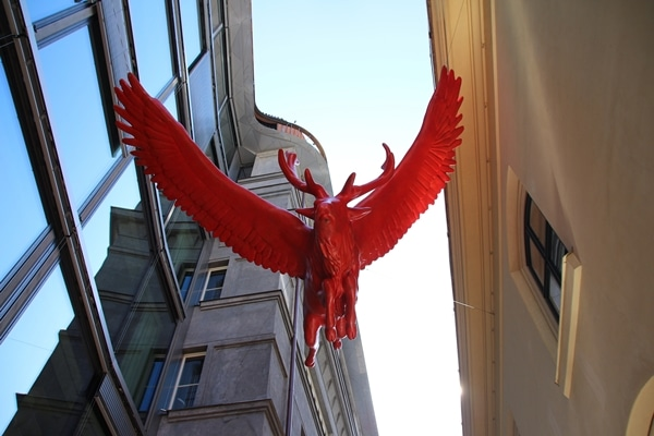 a red statue of a bull hanging above
