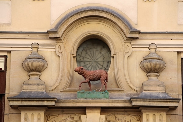 a statue of a red sheep over a doorway