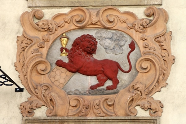 closeup of a red lion holding a gold chalice