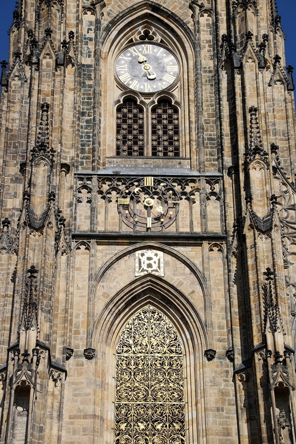 closeup of a clock on the exterior of a large stone church