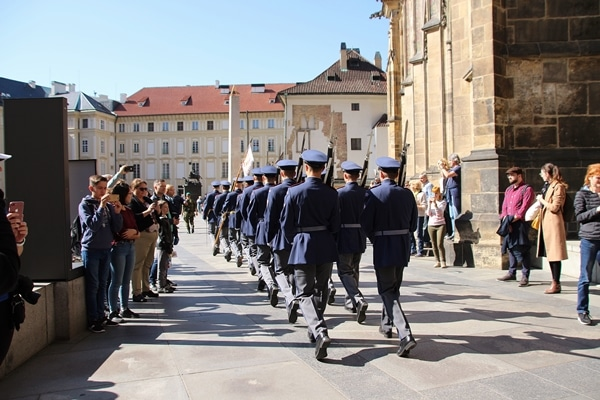 soldiers in blue uniforms marching through a square
