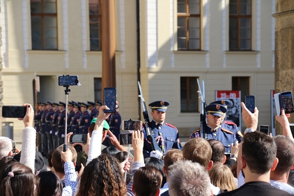 A group of people watching a ceremony with soldiers